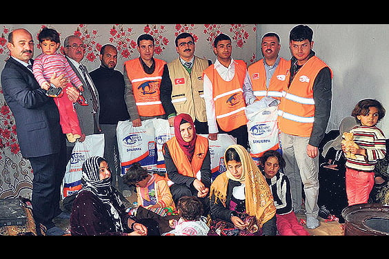 """Members of a Turkish family distribute aid packages to a Syrian """"sister family,"""" a project organized by the Kimse Yok Mu charity. (Photo: AA, Müslüm Etgü)"""
