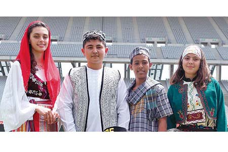 Some of the students who are taking part in this year's International Turkish Olympiads pose for photos while one of them speaks to a reporter at Atatürk Olympic Stadium in İstanbul on Wednesday. (Photo: Cihan)