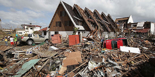 Survivors stand outside their damaged house at typhoon-hit Tacloban city, Leyte province central Philippines on Monday. (Photo: AP)