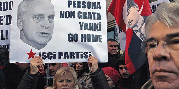 A Turkish protester holds a sign with a photo of US Ambassador Francis Ricciardone during a protest held by leftist Workers' Party outside the US Embassy in Ankara on Dec. 23, 2013. (Photo: AP)