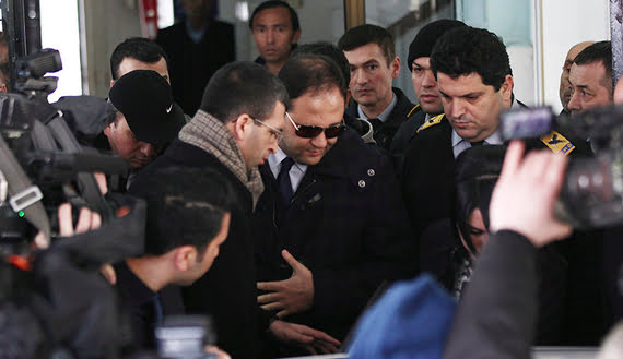 Baris Guler (C in sunglasses), son of Turkey's Interior Minister Muammer Guler, is escorted by plainclothes police officers as he leaves a medical check-up in Istanbul, Dec. 16, 2013.  (photo by REUTERS/Kursat Bayhan/Zaman Daily via Cihan News Agency)