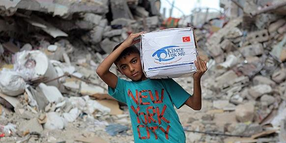 A Palestinian kid carries an aid package delivered by Kimse Yok Mu? charity organization in Gaza. (Photo: Today's Zaman, Mehmet Ali Poyraz)