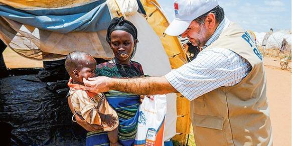 A Kimse Yok Mu volunteer hands out sacrificial meat to Somali refugees taking shelter in a Kenyan refugee camp on Eid al-Adha. (Photo: Today's Zaman)