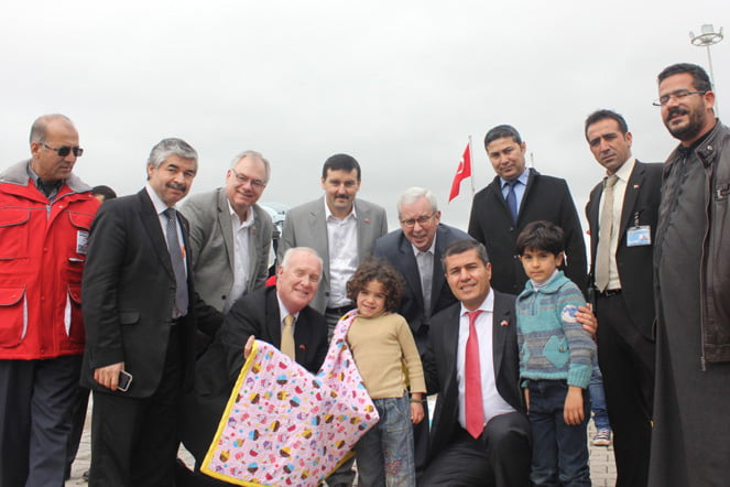 Former Purcellville mayor Robert W. Lazaro and Loudoun Board of Supervisors Chairman Scott K. York (center background, both in glasses) at a refugee camp in Turkey, handing out blankets collected last fall. (Courtesy of Northern Virginia Regional Commission)