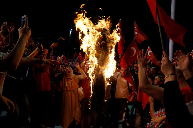 Supporters of Turkish President Tayyip Erdogan shout slogans over a burning effigy of U.S.-based cleric Fethullah Gulen during a pro-government demonstration at Taksim Square in Istanbul, Turkey, July 20, 2016. REUTERS/Ammar Awad