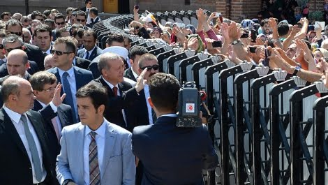 Escorted by an army of guards Erdogan is greeting the public from behind dividers.