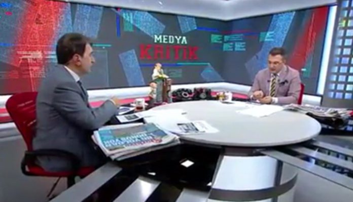 Cem Küçük (R) reads a message from a prosecutor during TV program.